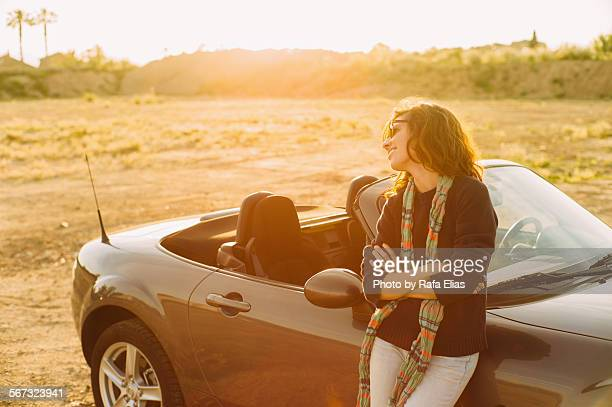 Pretty smiling woman standing with convertible car