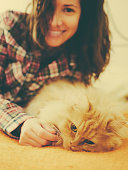 Pretty smiling woman with persian cat