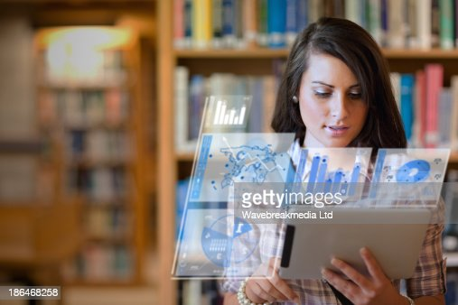 Pretty student working on her futuristic tablet : Stock Photo