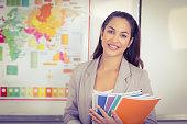 Portrait of pretty teacher holding notepads in a classroom in school