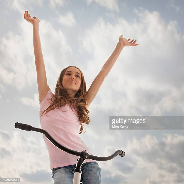 Pretty teenage girl with her arms raised while sitting on bike