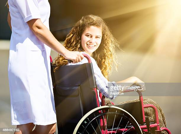 Pretty teenager being pushed in wheelchair looks around, smiling