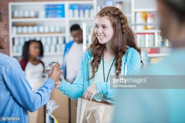 Jolie adolescente fait don conserves au cours de la collecte d'aliments communautaire