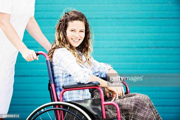 Pretty teenager in wheelchair being pushed by nurse