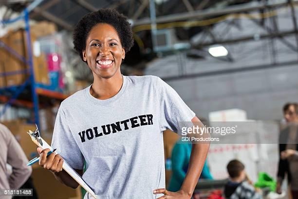bonita voluntaria en comida y ropa en automóvil