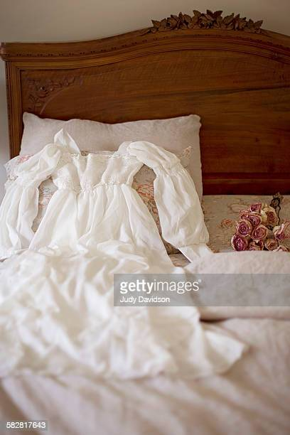 Pretty white dress on bed with dried flowers