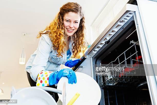 Mujer de negocios bastante con lavaplatos; que es vida doméstica.