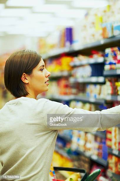 Pretty woman choosing products in a supermarket