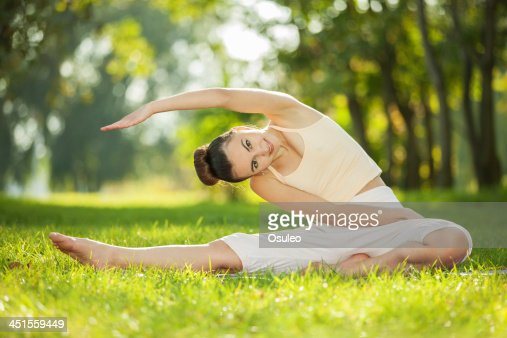 Pretty woman doing yoga exercises in the park : Stock Photo