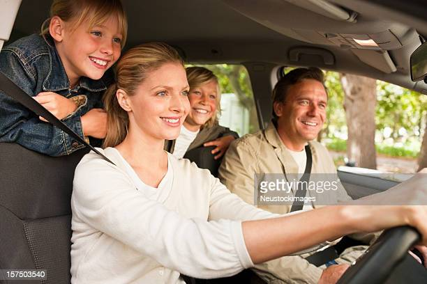 Pretty woman driving her family in a car