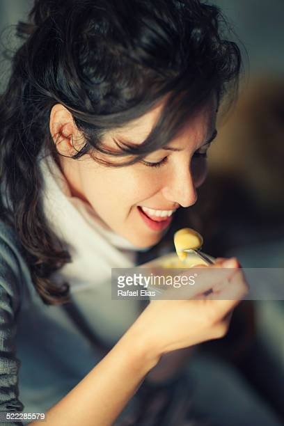 Pretty woman eating custard