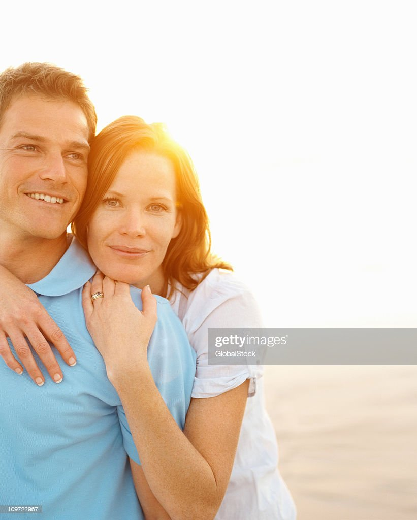 Pretty woman hugging her husband from behind on beach : Stock Photo