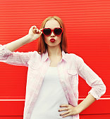 Pretty woman in red sunglasses blowing lips kiss over colorful background ·  508102888  iStock  Jolie femme à lunettes de soleil ... 964b599be902