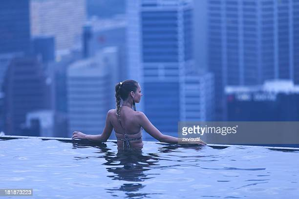 Pretty woman in swimming pool looking out over cityscape