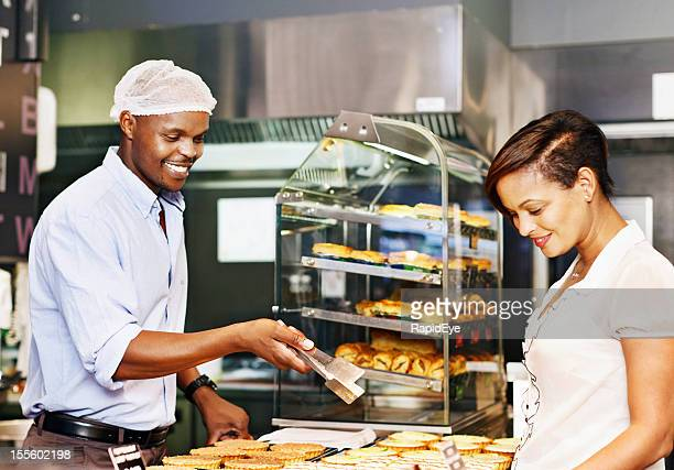 Pretty woman is helped to choose confectionery by handsome baker