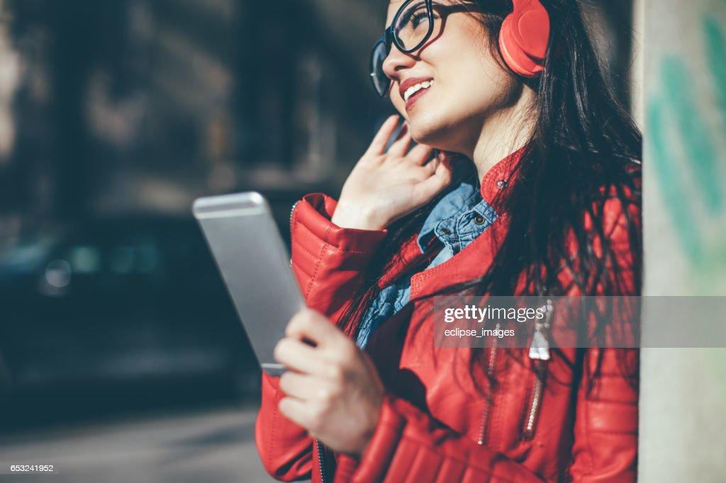 Pretty woman listening music with earphones from a phone : Bildbanksbilder