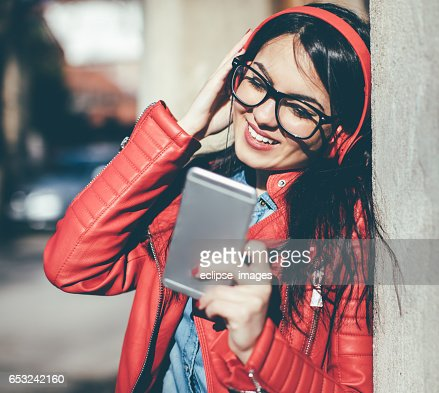 Pretty woman listening music with earphones from a phone : Stock-Foto