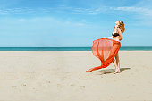a beautiful woman with perfect body standing at seashore enjoying holiday vacation on a sunny day
