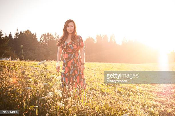 Pretty woman picking wildflowers in meadow at sunset