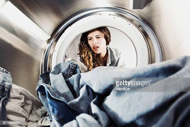 Pretty woman pulling face at laundry in drier