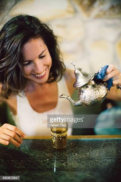 Pretty woman serving tea