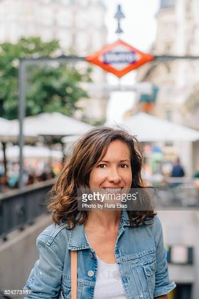 Pretty woman smiling by subway entrance