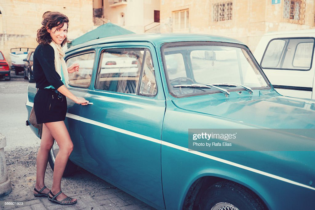 Pretty woman standing by classic car