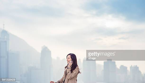Pretty woman talking on smartphone in urban city