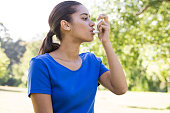Pretty woman using her inhaler on a sunny day