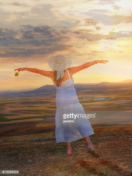 Pretty woman with a pink flying over the fields of Castilla sunset