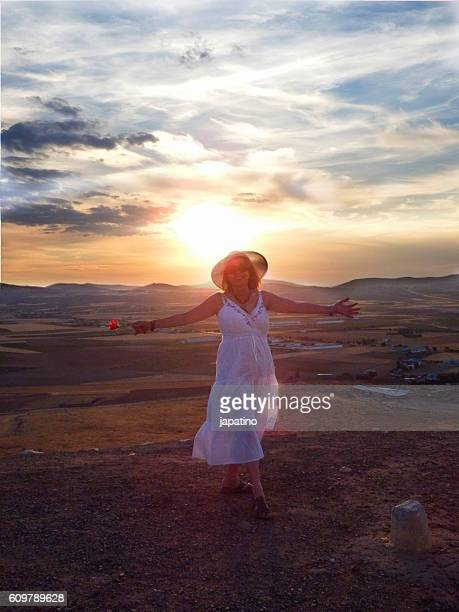 Pretty woman with a rose looking at the Windmills at sunset