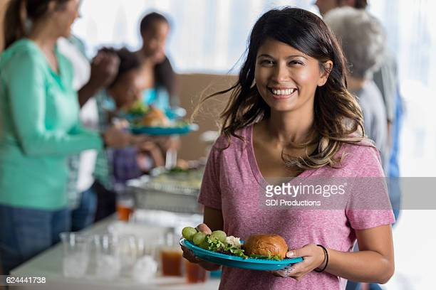 Pretty woman with plate of healthy food in soup kitchen