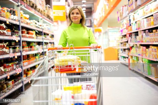 Pretty woman with shopping trolley walking at a supermarket.