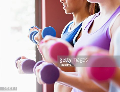 Pretty women lift pastel weights in all-female gym