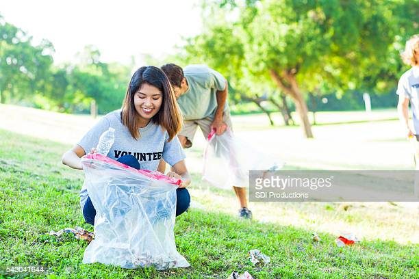 Pretty young Asian female volunteer picks up trash in park
