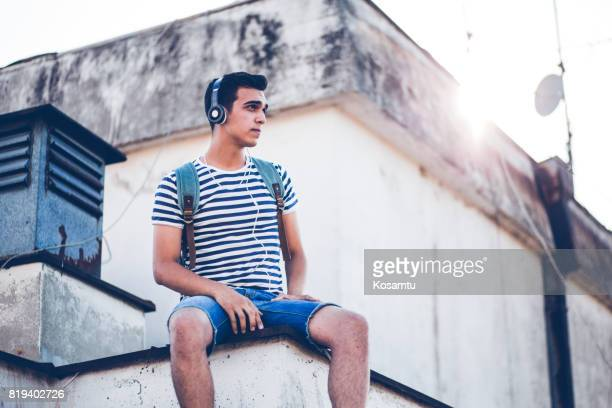Pretty Young Boy Listening To Music And Resting On Rooftop