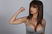 Strong and beautiful. Pretty young brunette woman showing bicep on her arm
