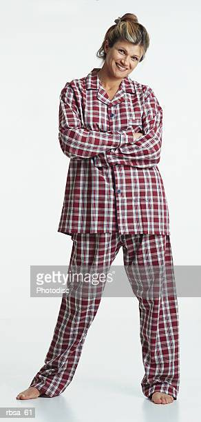 pretty young caucasian adult blonde female barefoot with hair up wearing red plaid pajamas stands with arms folded looking at the camera with a humorous smile
