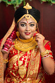 A pretty young female model wearing traditional indian / Bangladeshi bridal outfit with heavy jewelry and makeup