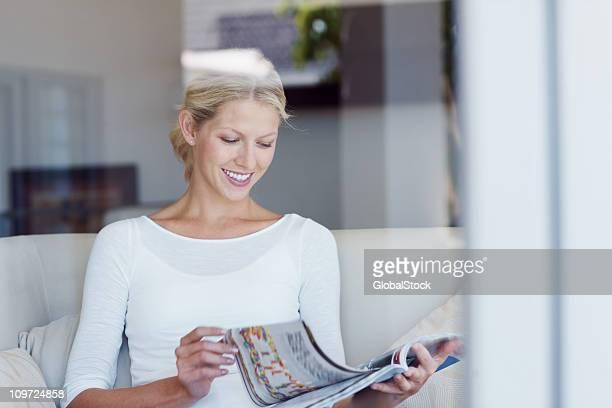 Hübsche junge weibliche Lesen einer Zeitschrift wie zu Hause fühlen.