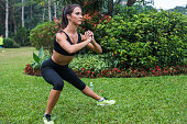 Pretty young fit woman doing stretching exercises in park. Fitness woman doing side lunges outdoors