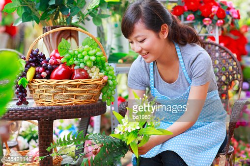 pretty young florist working in the shop : Stock Photo
