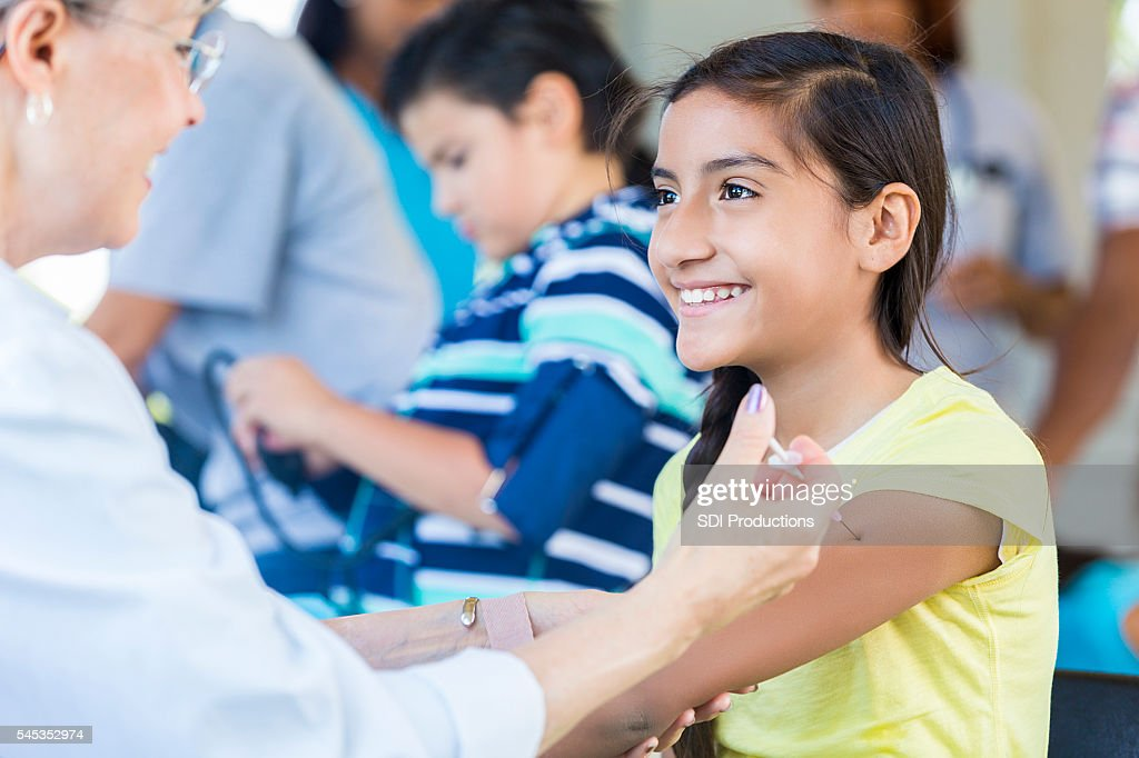 Pretty young girl getting her flu shot at free clinic