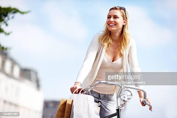 Hübsche Junge Frau wegsehen, während Reiten Fahrrad