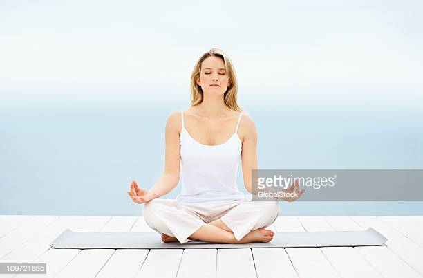 Pretty young girl sitting in lotus position on a dock