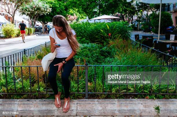 Pretty young girl sitting in Vara de Rey promenade while looking at mobile phone