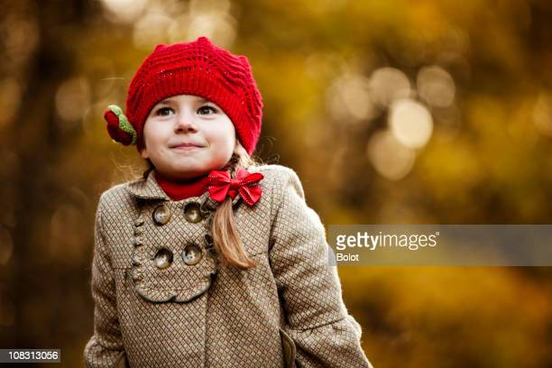 Pretty young girl wearing brown coat and red hat in a park