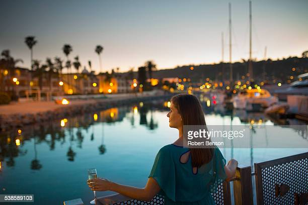 A pretty young girl with a drink in her left hand stands by the marina iron railing.