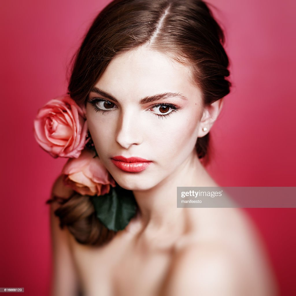 pretty Young girl with pink roses in hair : Stock Photo