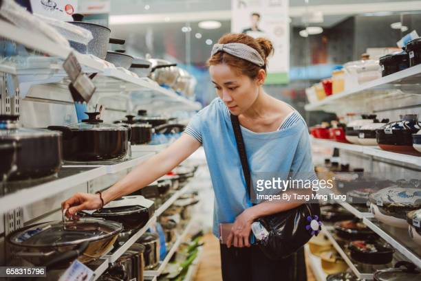 Pretty young lady choosing kitchenware in a department store.